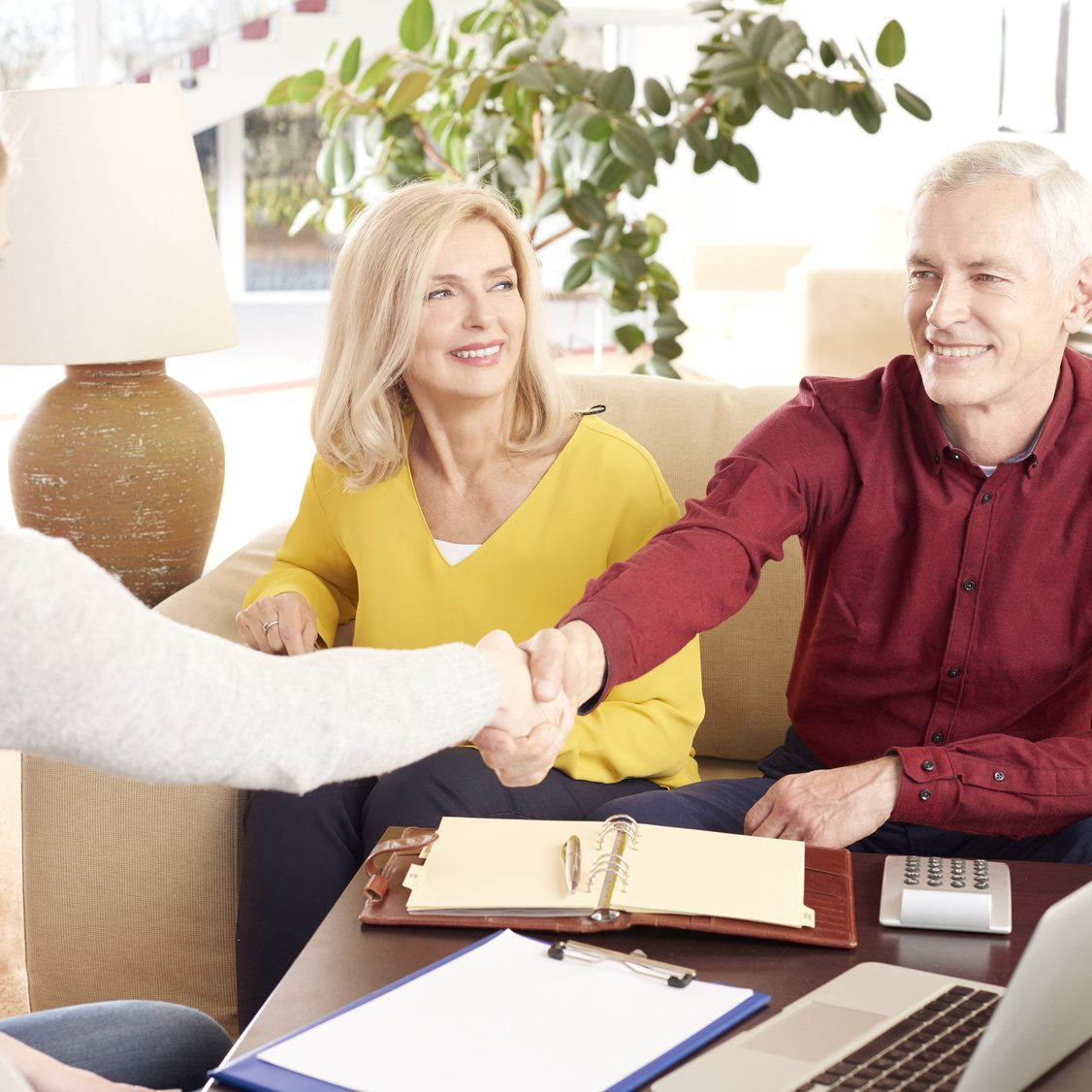 Shot of an elderly couple sitting at home and consulting with their financial advisor about savings. Senior man and businesswoman shaking hands.